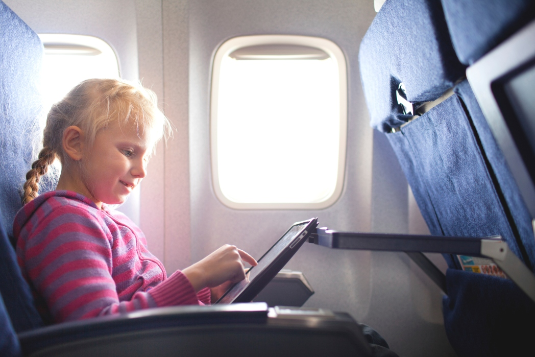 Girl plays tablet on plane