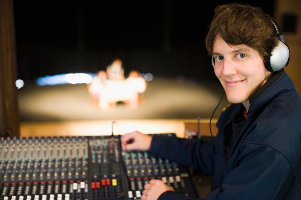 Portrait of a man at a sound mixer in a recording studio